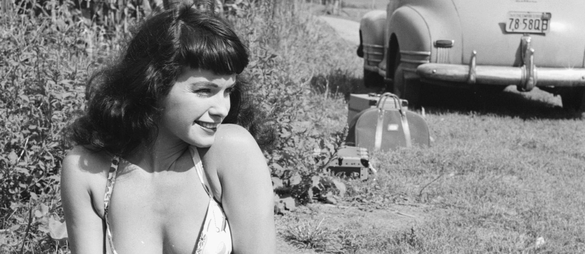 American pin-up Bettie Page, Playboy playmate of the month for January 1955, sunbathes in a country lane, New York state, 1956. (Photo by Weegee(Arthur Fellig)/International Center of Photography/Getty Images)